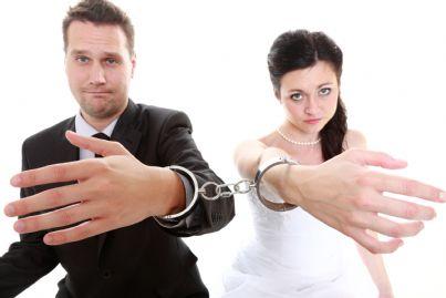 coppia di sposi con manette che chiede liberazione simbolo divorzio consensuale