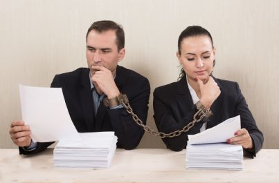 uomo e donna in manette che guardano carte divorzio