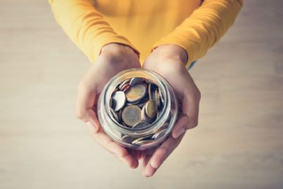 donna che tiene tra le mani soldi per donazione