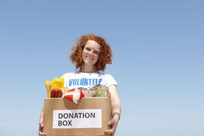 ragazza felice che dona una scatola con alimenti