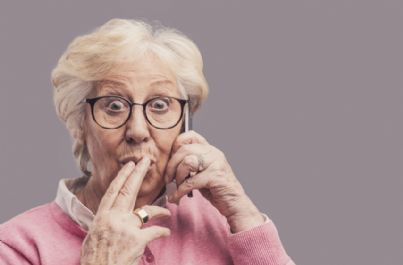 donna anziana al telefono stupita