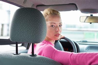 donna guarda indietro mentre fa retromarcia con auto