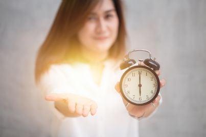 donna dona con in mano una sveglia