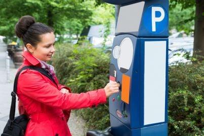 donna inserisce soldi parchimetro per parcheggio auto