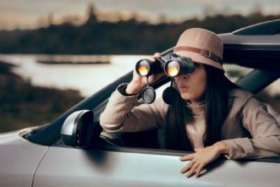 donna in macchina guarda con binocolo
