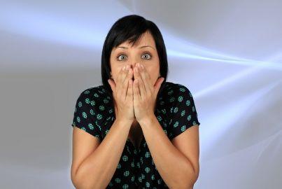 Donna sorpresa con le mani davanti alla bocca