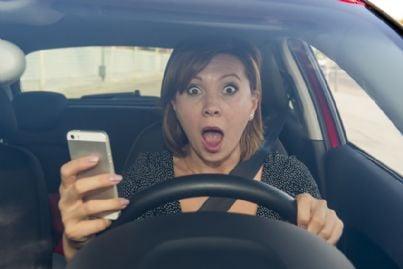 donna al telefono mentre guida spaventata