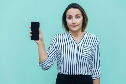 donna mostra seccata il proprio telefono