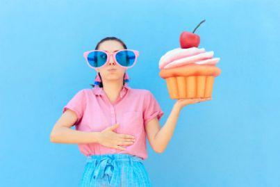 donna con in mano torta scaduta si tocca la pancia