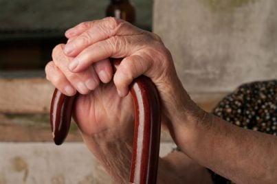 donna anziana con le mani sul bastone