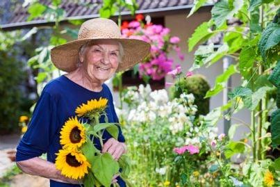 donna anziana felice di piantare fiori in giardino