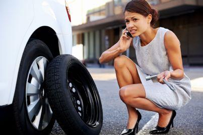 donna con auto con ruota bucata