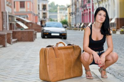 donna via di casa con valigia in strada concetto divorzio