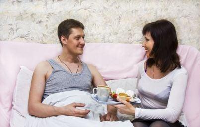 donna che porta colazione a letto al suo uomo