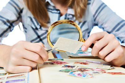 donna guarda la propria collezione di francobolli
