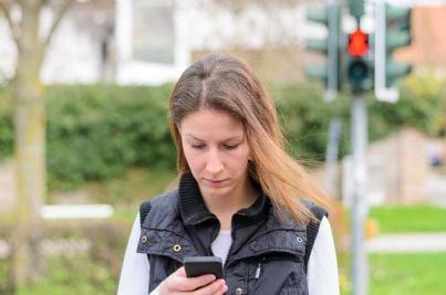 donna col cellulare attraversa la strada distratta