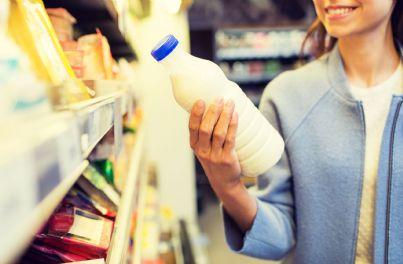 donna al supermercato guarda etichetta del latte
