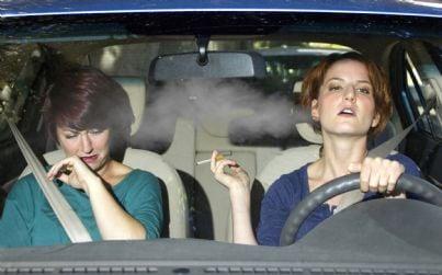 donna che fuma in auto con passeggero infastidito