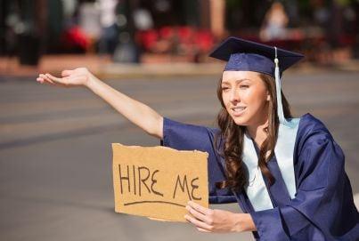 donna laureata con cartello che dice cerco lavoro