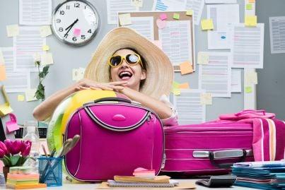 donna al lavoro con le valigie sogna le vacanze