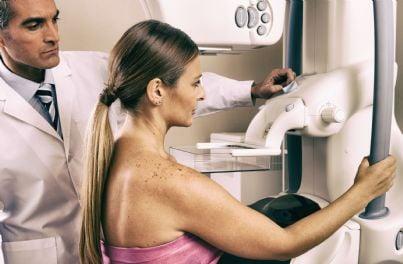 medico che assiste donna mentre fa mammografia