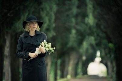donna che porta fiori in un cimitero