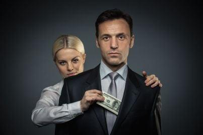 donna che prende soldi dalla tasca della giacca di un uomo