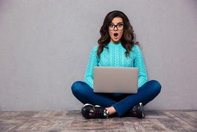 donna scioccata che guarda il proprio computer