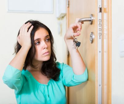 donna guarda sconvolta serratura rotta della porta di casa
