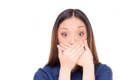 donna mette mani sulla bocca dalla sorpresa