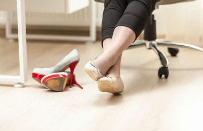 donna toglie tacchi e indossa scarpe basse in ufficio