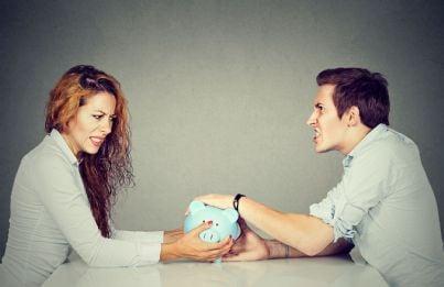 donna e uomo lottano per tenere salvadanaio