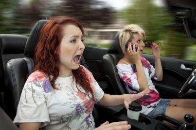 donna alla guida distratta con telefono