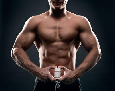 uomo muscoloso con flacone di anabolizzanti in mano