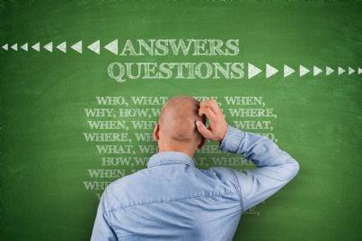 uomo con dubbi di fronte a lavagna con domande e risposte