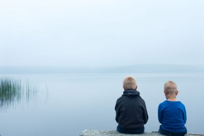 due fratelli seduti di fronte al lago