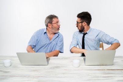 due uomini davanti al computer in ufficio che si guardano sorpresi