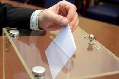 Elettore che inserisce la scheda nell'urna