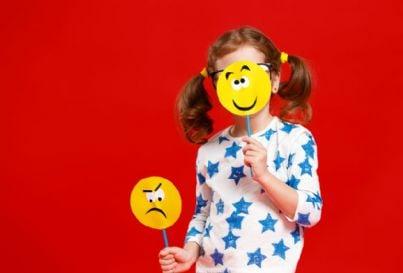 bambina esprime emozioni con cartelli emoji