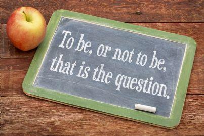 essere non essere di Amleto scritta su una lavagnetta con a fianco una mela