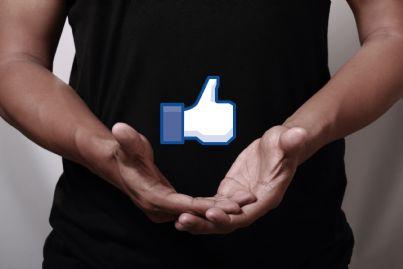 uomo che tiene tra le mani il simbolo di facebook