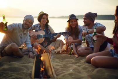 giovani che fanno falò in spiaggia