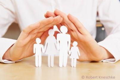 Mani che coprono in segno di protezione una famiglia simboleggiata da ritagli di carta