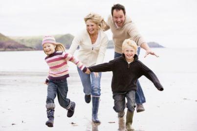 Famiglie che corre sulla spiaggia