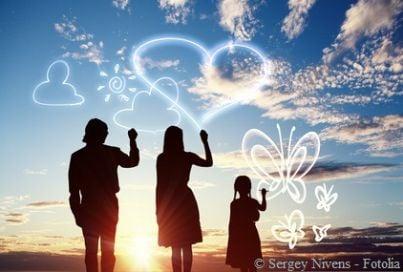 Famiglia che scrive nel cielo davanti a un tramonto