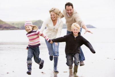 Famiglia che corre sulla spiaggia
