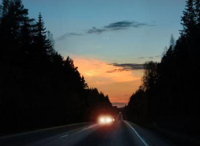 i fari di una macchina su strada notturna