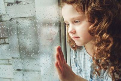 bambina triste che guarda dietro la finestra