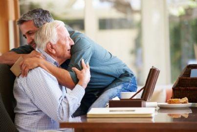 figlio abbraccia il padre anziano