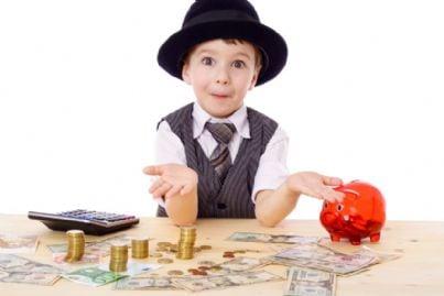 bambino con cappello mette soldi nel salvadanaio